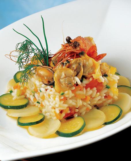 Riso di mare con verdurine su un letto di zucchini e patate